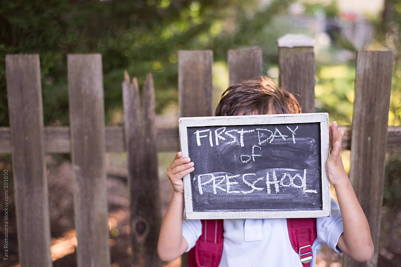 boy hides face behind first day of preschool sign by Tara Romasanta for Stocksy United