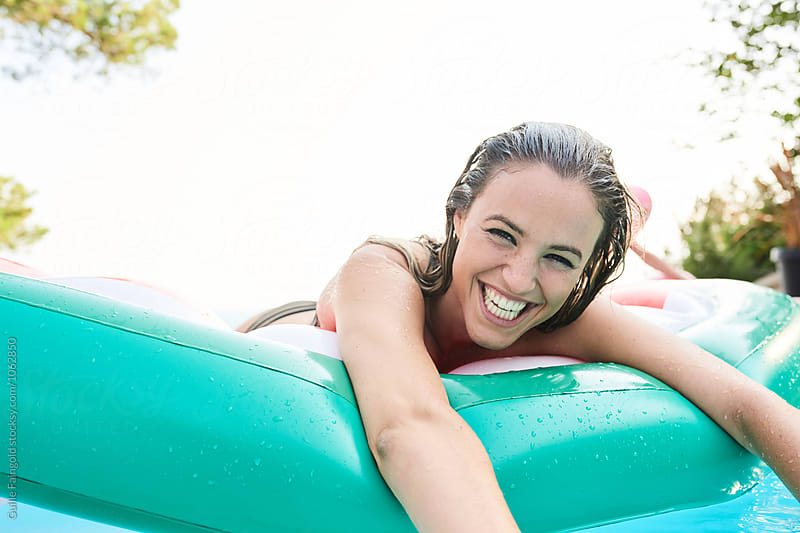 Beautiful wet-haired girl smiling while lying on inflatable in pool by Guille Faingold for Stocksy United