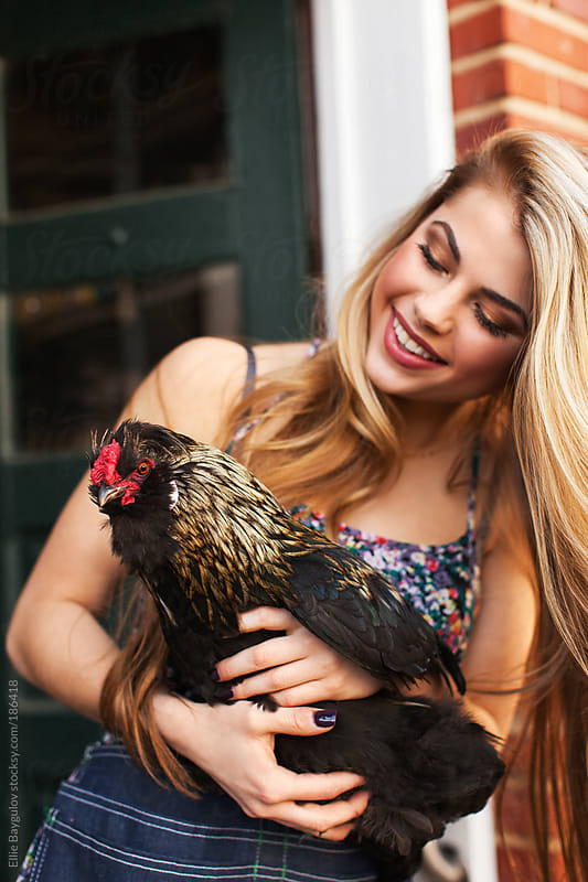 Beautiful blonde girl holding a chicken by Ellie Baygulov for Stocksy United