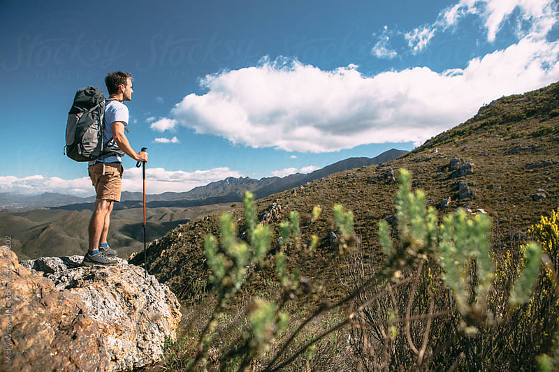 Hiker with backpack on a mountain side enjoying the view by Micky Wiswedel for Stocksy United