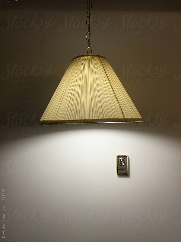 Hanging lamp and wall thermostat in a 60s era motel  by David Smart for Stocksy United