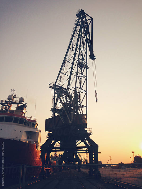 Cranes and container ship at sunset by Borislav Zhuykov for Stocksy United