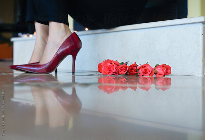 Woman in red heels with roses next to them sitting on the fireplace by Carolyn Lagattuta for Stocksy United