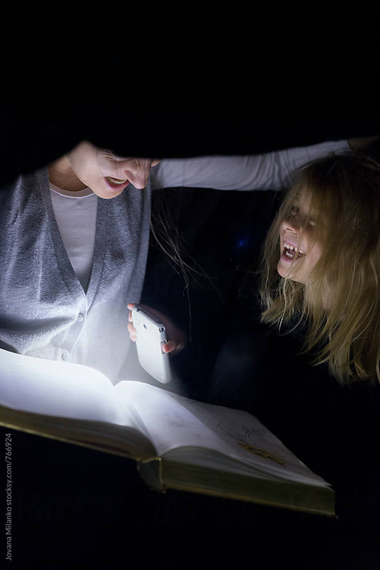 Mother reading Jack-o'-lantern story under the black bed linen to her kid on Halloween by Jovana Milanko for Stocksy United