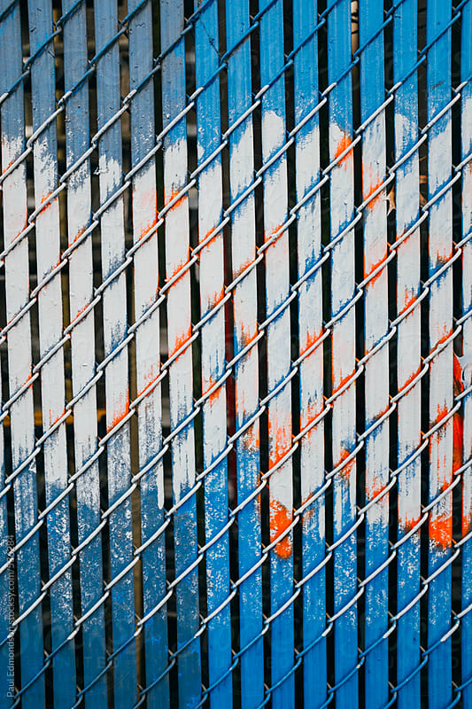 Blue chain-link fence and paint covering graffiti markings by Paul Edmondson for Stocksy United
