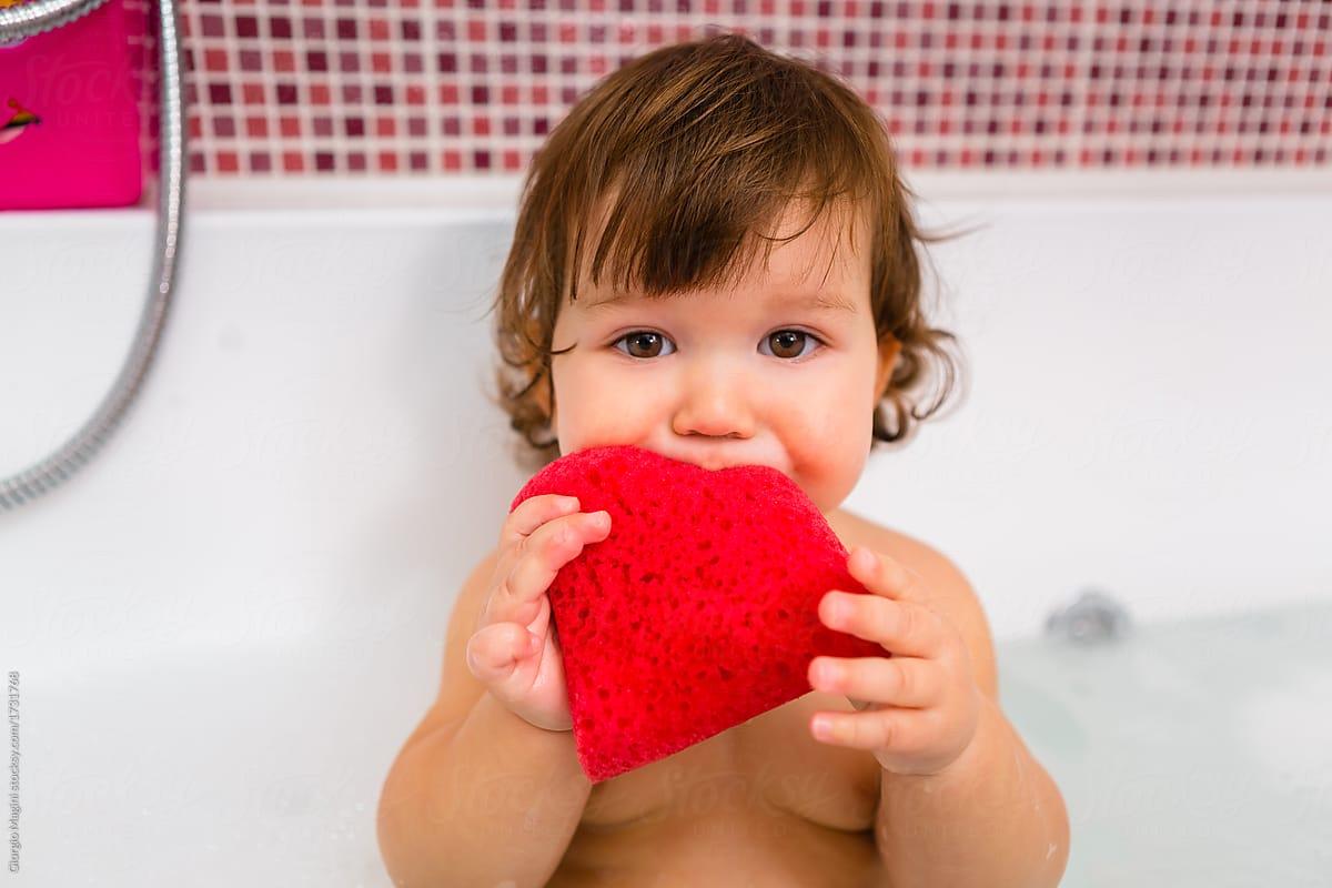 Cute Baby Girl In The Bathtub Biting A Red Sponge   Stocksy United