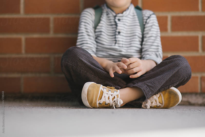 A little boy sitting cross legged in front of a brick wall wearing yellow sneakers by Ania Boniecka for Stocksy United