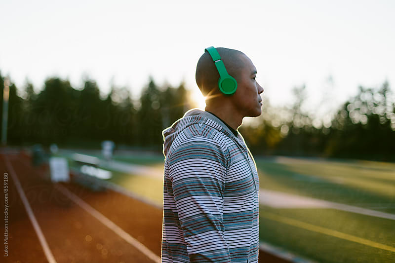 Man Listening To Music Through Headphones At Track And Field During Workout by Luke Mattson for Stocksy United