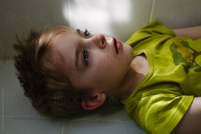 Close up of boy lying in dappled light on bathroom floor. by Julia Forsman for Stocksy United