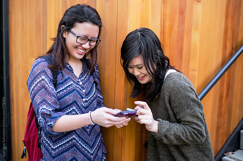 Happy college students looking at their phone on campus by Suprijono Suharjoto for Stocksy United