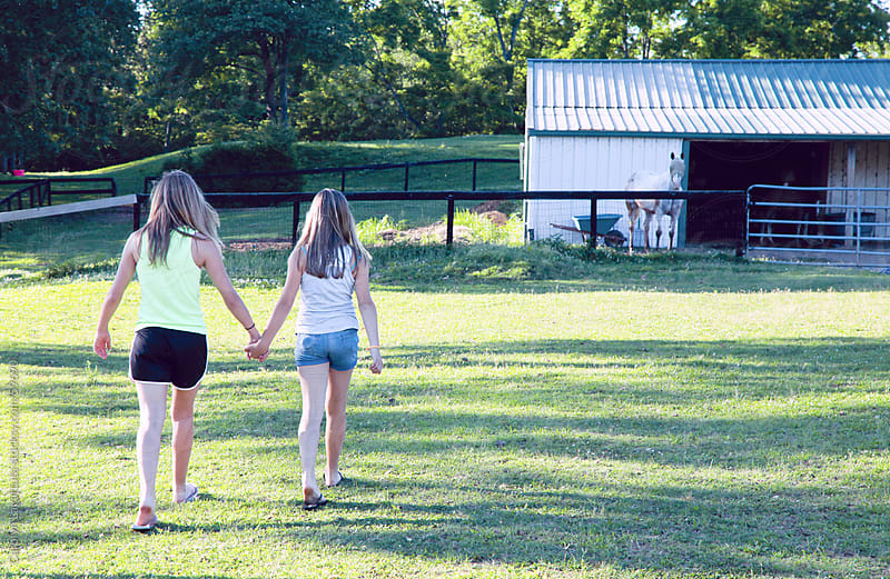Friends holding hands and walking to the barn to feed the horses by Carolyn Lagattuta for Stocksy United