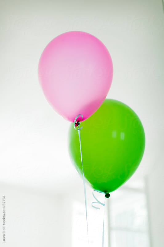 Complementary colours: green and pink balloons together  by Laura Stolfi for Stocksy United