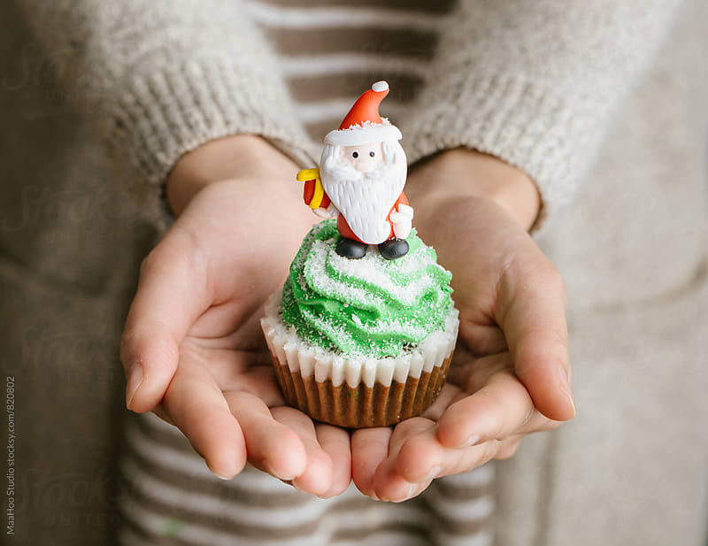 Woman holding christmas cupcake by Maa Hoo for Stocksy United