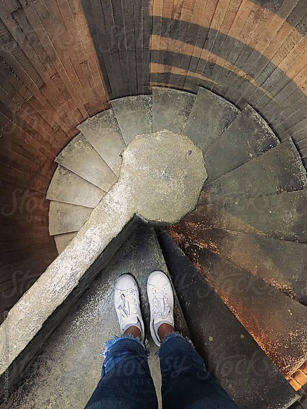woman standing on the beginning of swirly stairs stocksy united