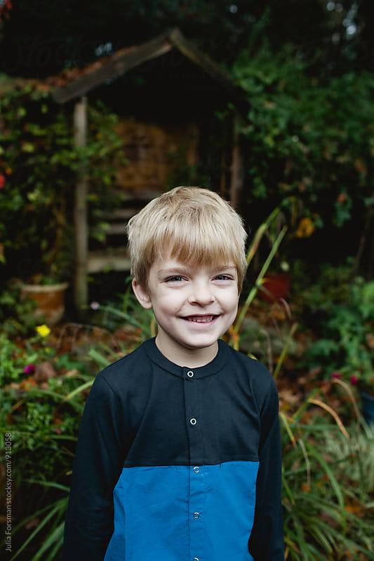 Happy portrait of boy in a garden. by Julia Forsman for Stocksy United