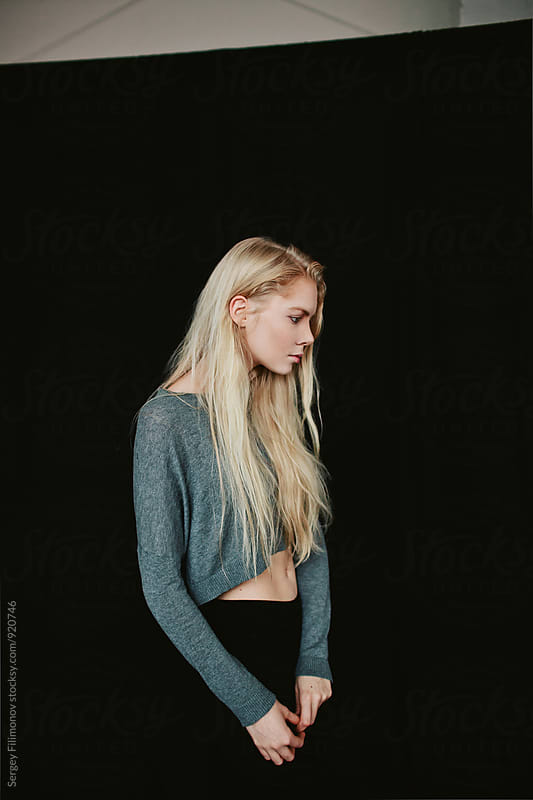 Portrait of a young blonde girl on a black background in the studio by Sergey Filimonov for Stocksy United