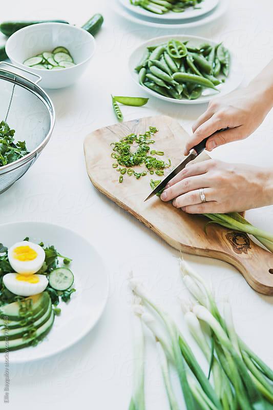 Woman cutting scallions for a salad by Ellie Baygulov for Stocksy United