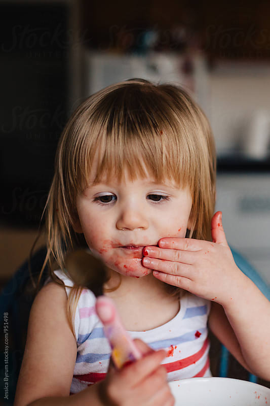 Cute toddler girl eats jello from a white bowl. by Jessica Byrum for Stocksy United