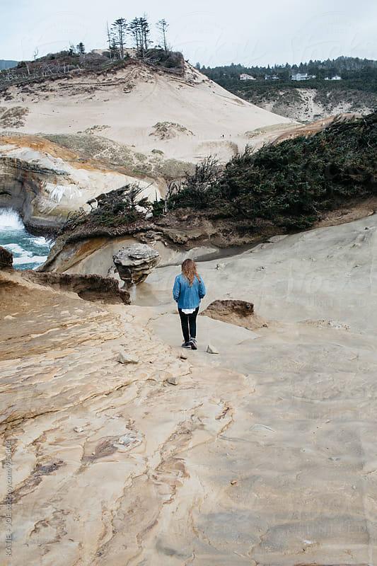 Woman walking down a rocky hill toward the ocean by KATIE + JOE for Stocksy United