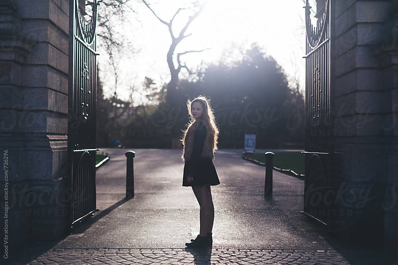Woman standing by the gate of park by Good Vibrations Images for Stocksy United