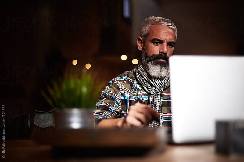 handsome man working with his laptop by Guille Faingold for Stocksy United