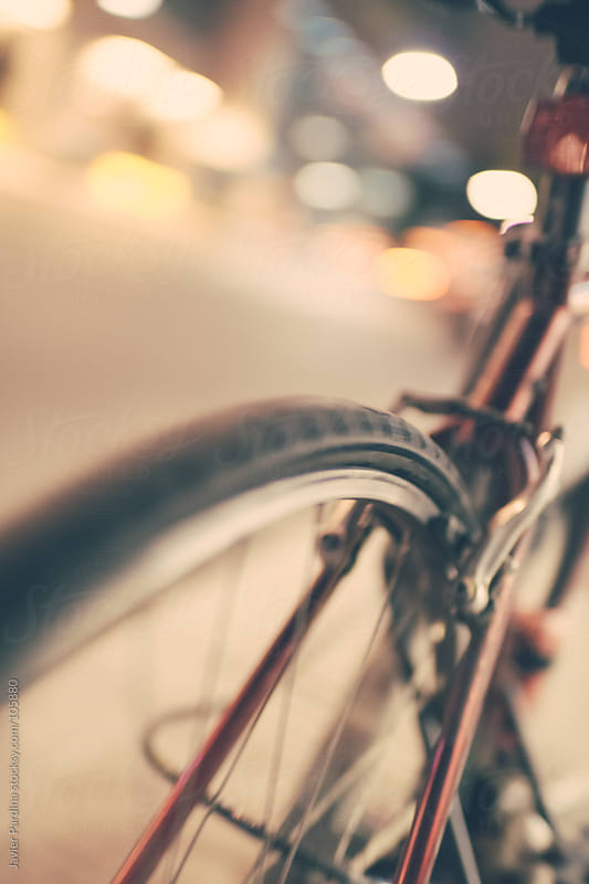 detail of a bicycle wheel at night by Javier Pardina for Stocksy United