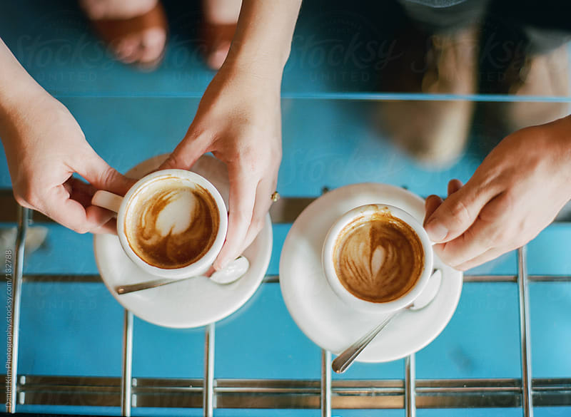 Hands holding lattes by Daniel Kim Photography for Stocksy United
