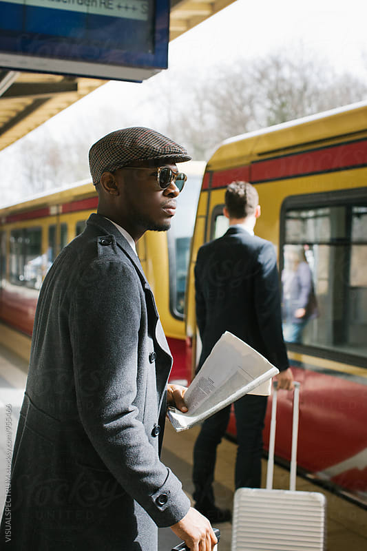 Stylish Young Black Businessman Standing in Train Station as Train is Arriving by VISUALSPECTRUM for Stocksy United