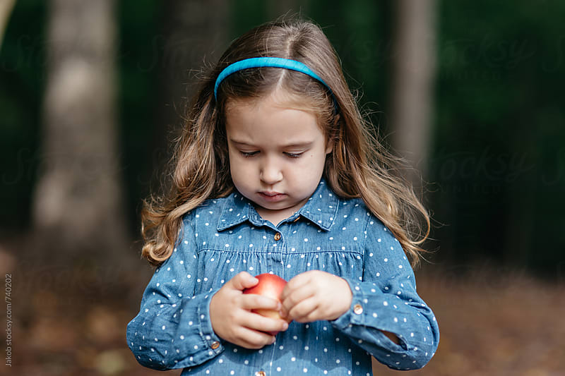 Cute young girl playing with her nectarine by Jakob for Stocksy United