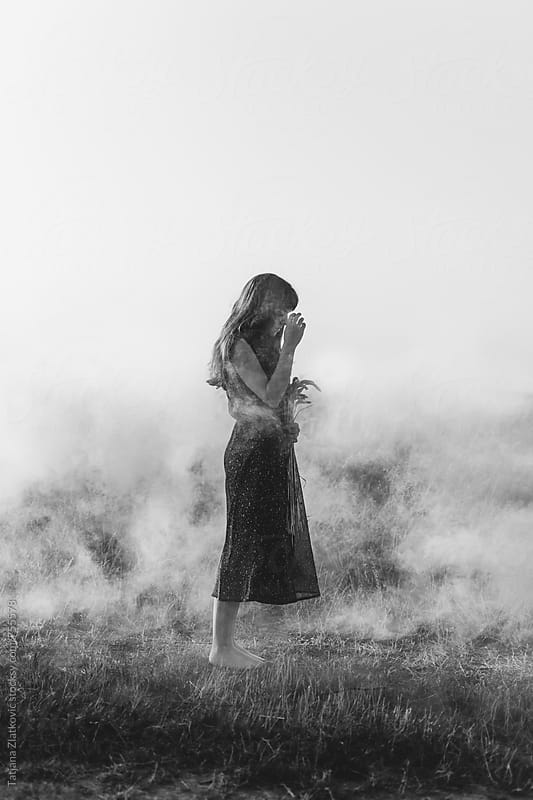 Young woman in a smoke cloud by Tatjana Zlatkovic for Stocksy United