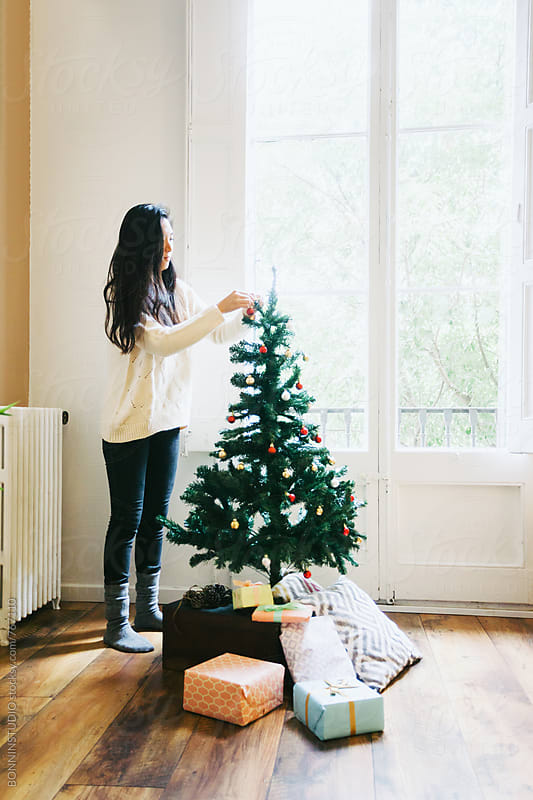 Asian woman decorating Christmas tree at home. by BONNINSTUDIO for Stocksy United