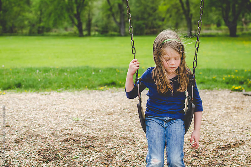 Child sitting on swing in the park by Lindsay Crandall for Stocksy United