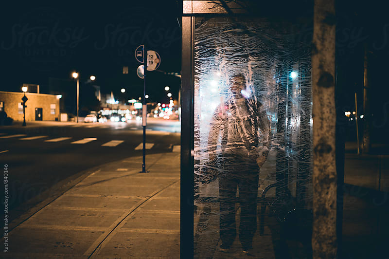 A shadowy figure stands behind the etched glass of a bus stop by Rachel Bellinsky for Stocksy United