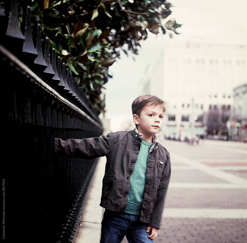 Young boy portrait on wrought iron fence in downtown Washington DC by Cameron Whitman for Stocksy United