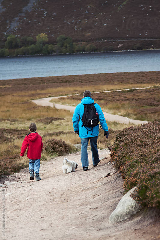 Father and son walking in the Scottish Highlands by Ruth Black for Stocksy United