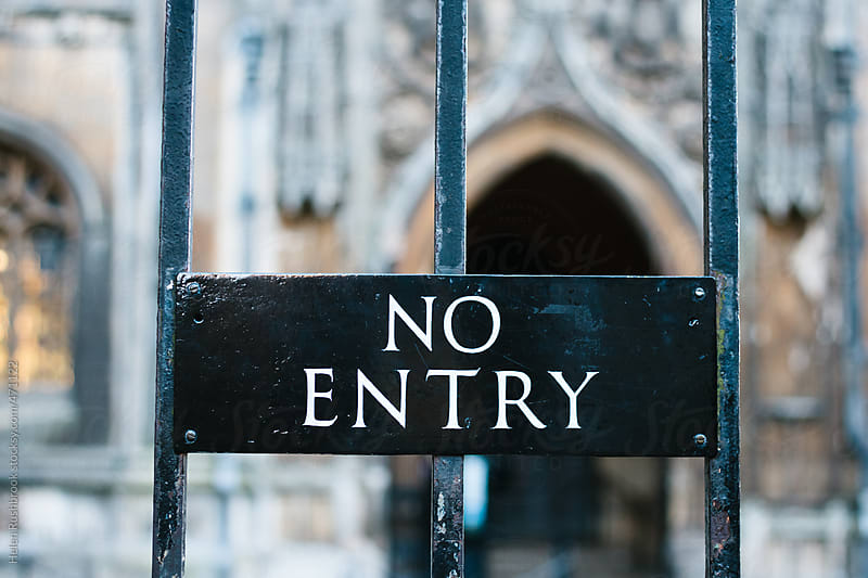 A no entry sign in front of a church by Helen Rushbrook for Stocksy United