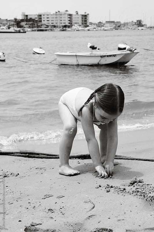Little Girl Playing in Sand At A Bay by Dina Giangregorio for Stocksy United