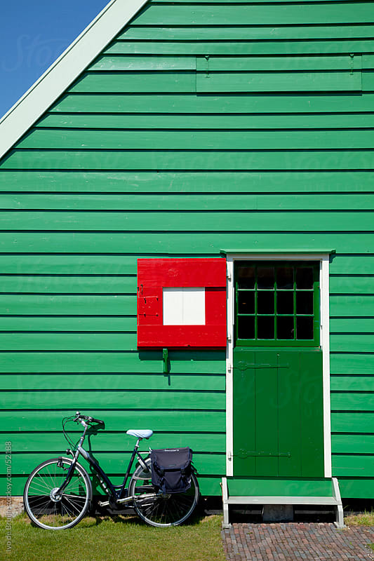 A green wooden house with a green door and a red shutter with a bike in front by Ivo de Bruijn for Stocksy United
