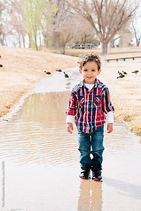 boy stands in a puddle by Tara Romasanta for Stocksy United