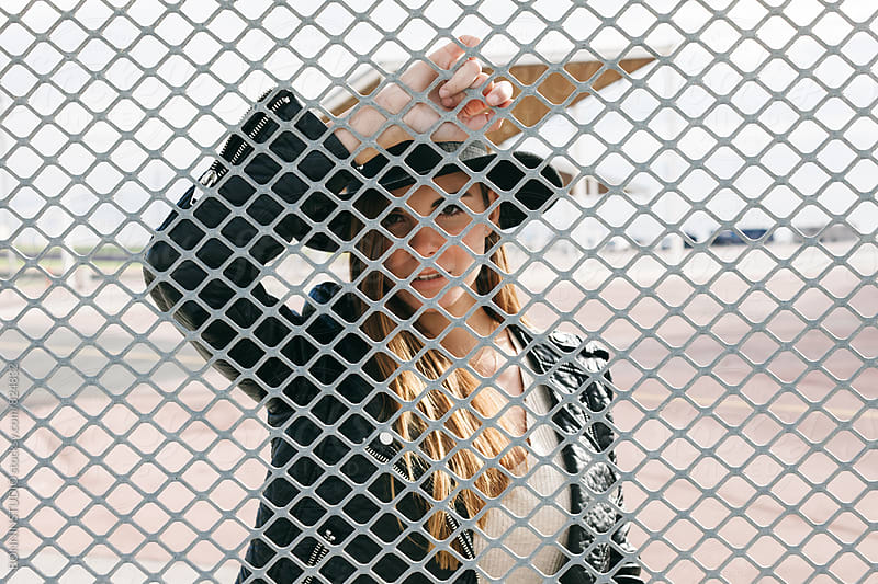 Portrait of an alternative caucasian female standing through a fence. by BONNINSTUDIO for Stocksy United