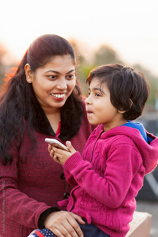 Mother and daughter sharing a cheerful moment outdoors by Saptak Ganguly for Stocksy United