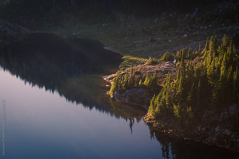 Distant tent perched on a cliff overlooking a lake at sunset by Christian Tisdale for Stocksy United