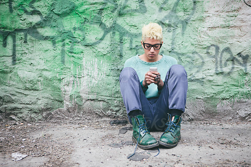 Stylish Young Man with Bleached Blond Hair Using Cellphone Technology while Sitting on the Ground by Joselito Briones for Stocksy United