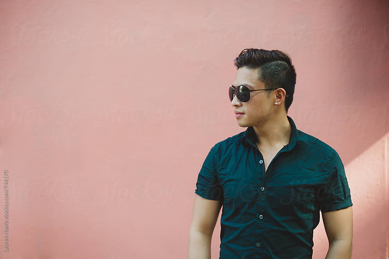 Young man in sunglasses standing against pink wall by Lauren Naefe for Stocksy United