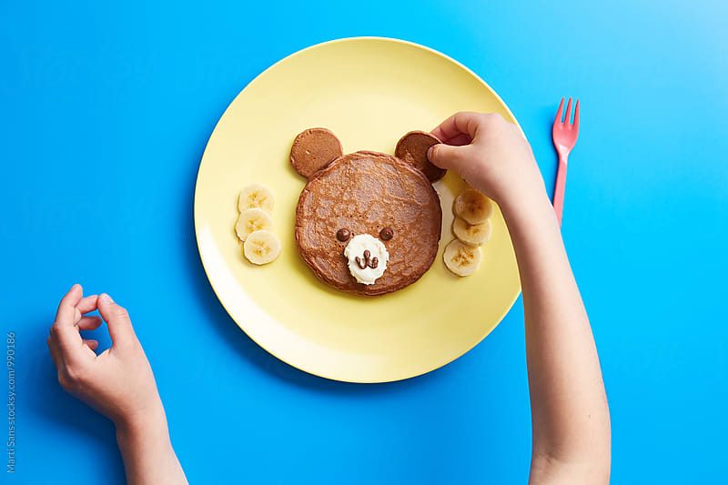 Kid making bear from pancake by Martí Sans for Stocksy United