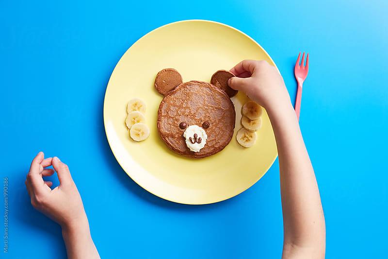 Kid making bear from pancake by Martí Sans for Stocksy United