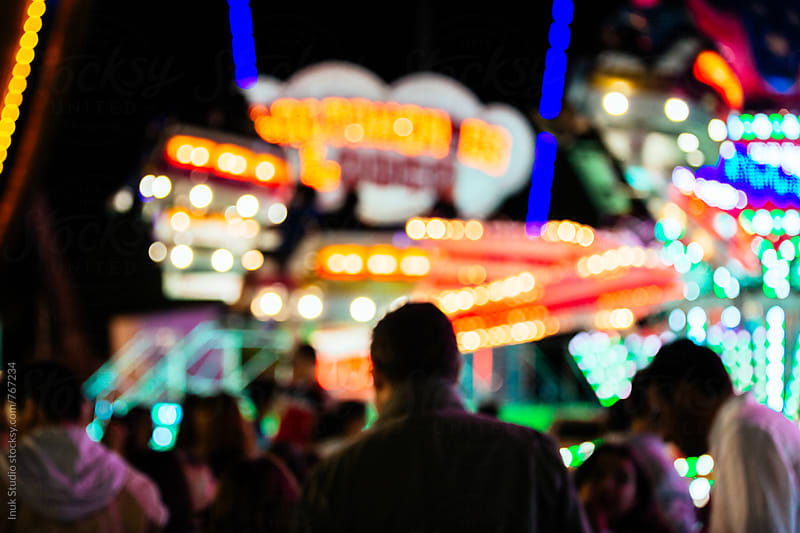 Blurred people in a fair at night by Inuk Studio for Stocksy United