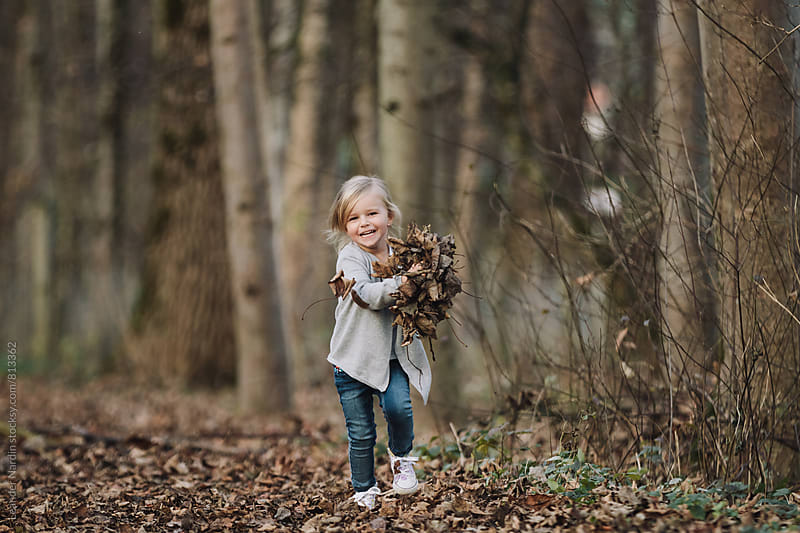 blonde cute little girl running through a forest hands full with foliage by Leander Nardin for Stocksy United