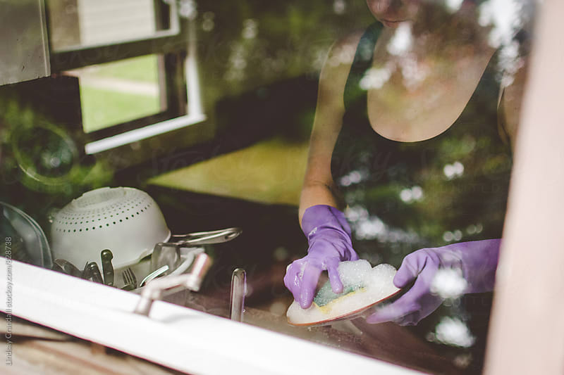 Woman washing dishes through a window by Lindsay Crandall for Stocksy United