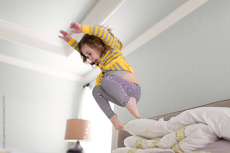 Cute toddler playing on a bed by Jakob for Stocksy United